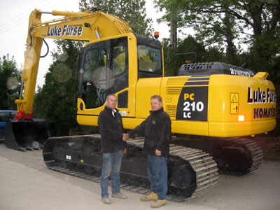 Luke Furse hands over the keys of the new excavator to Alan Gliddon